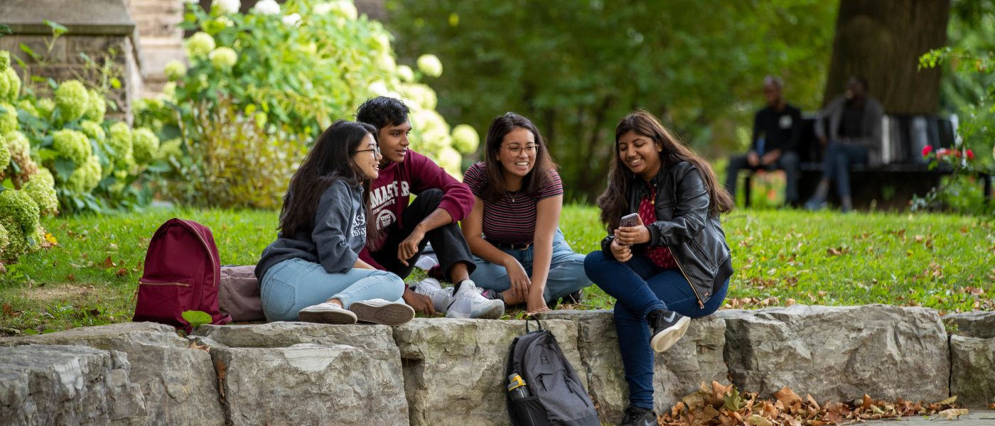 Students sitting in a garden on campus