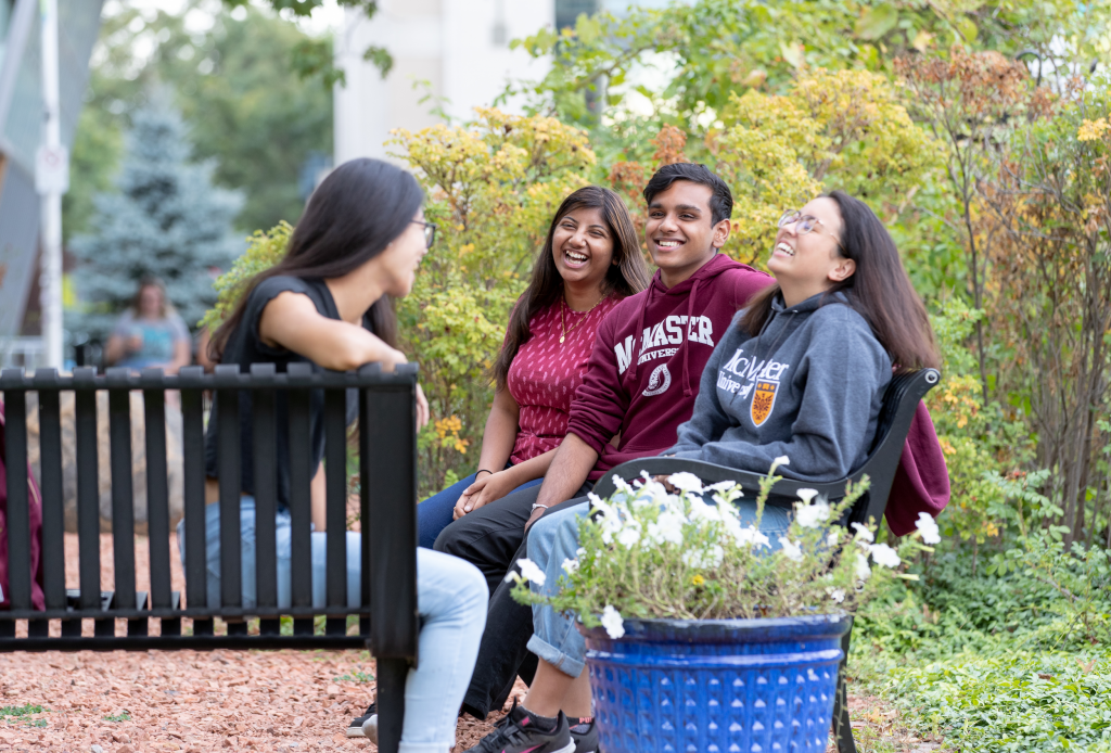 Students sitting on ground or along rocks or benches near and around University Hall
